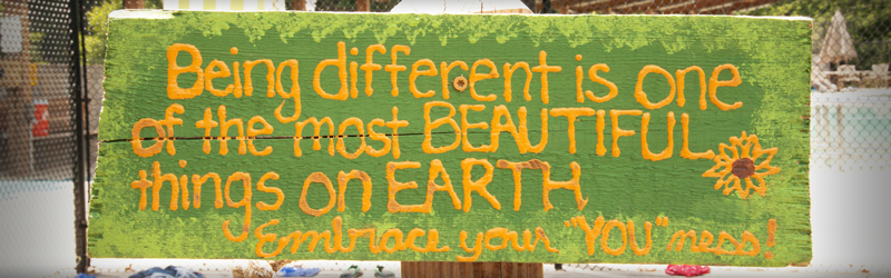 Painted green sign with yellow flower and text 'Being different is one of the most beautiful things on Earth; Embrace your you-ness'