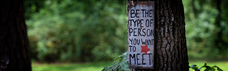 Painted sign on tree with text 'Be the type of person you want to meet'